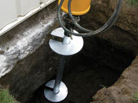 Installing a helical pier system in the earth around a foundation in Belgrade