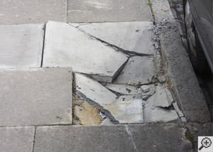 photo of a sinking concrete sidewalk with cracks in Lewistown
