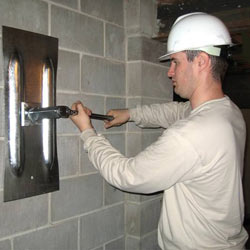 installing a wall anchor to repair an bowing foundation wall in Livingston