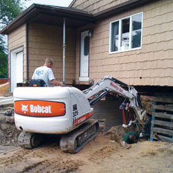 Excavating to expose the foundation walls and footings for a replacement job in Cody