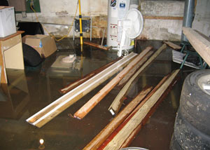 A severely flooding basement in Laurel, with lumber and personal items floating in a foot of water