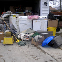 Soaked, wet personal items sitting in a driveway, including a washer and dryer in Butte.